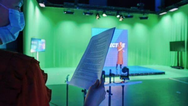 EI Agency - Online event persoon met script in handen voor een presentatrice